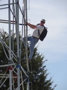 Denny Hoar of the NGS places an antenna on the top to collect GPS data overnight.