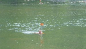 Nathan Harris, of Allegheny Surveys, swims in place while locating river bottom cross sections downstream of the dam.