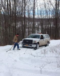 RETTEW surveyor John Vogt shovels snow in Delaware County so he can measure the boundary of land acquired to protect the watershed.