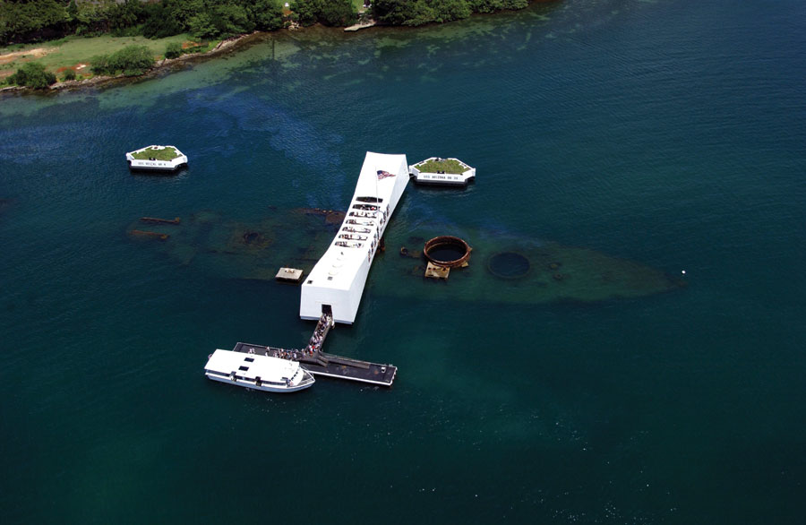 An aerial view of the USS Arizona Memorial with a US Navy Tour Boat, USS Arizona Memorial Detachment, moored at the pier as visitors disembark. Credit: JAYME PASTORIC, USN