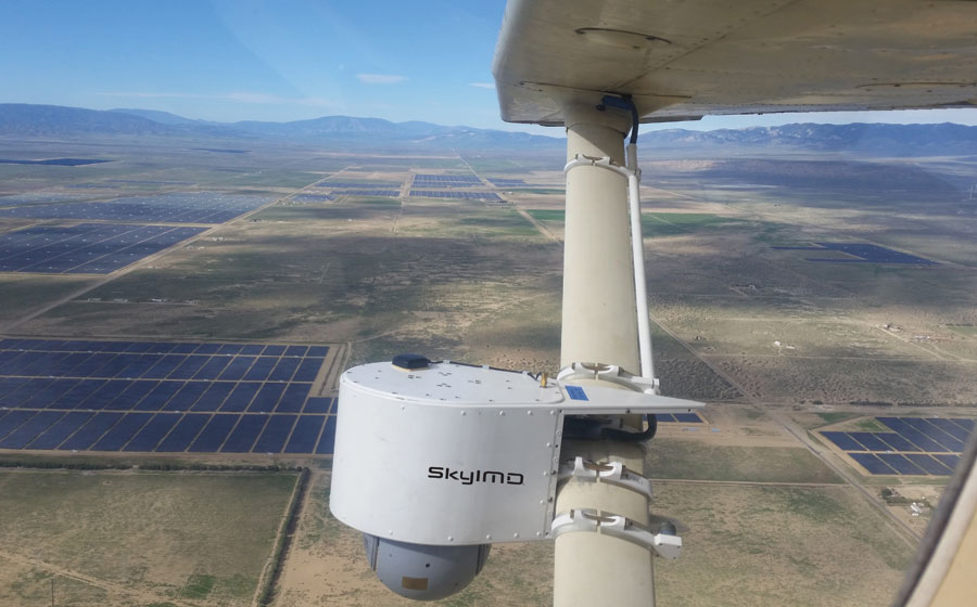 The sensor pod is strut-mounted on a fixed wing aircraft during a solar power plant aerial thermal IR inspection flight.