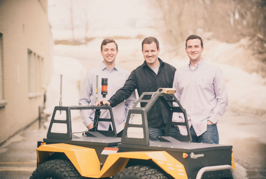 The active founders of Clearpath Robotics pose with a robotic utility vehicle (1 to r): Bryan Webb, Ryan Gariepy, and Matt Rendall.