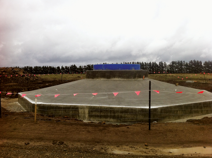 Wind turbine 2's finished foundation. Still wrapped in protective blue plastic is the embed ring, the steel cylinder upon which the first turbine tower segment is bolted.