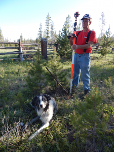 Survey dog 'Nash takes a break as the author marks the old pipe; the new pin is under the fence in the background.
