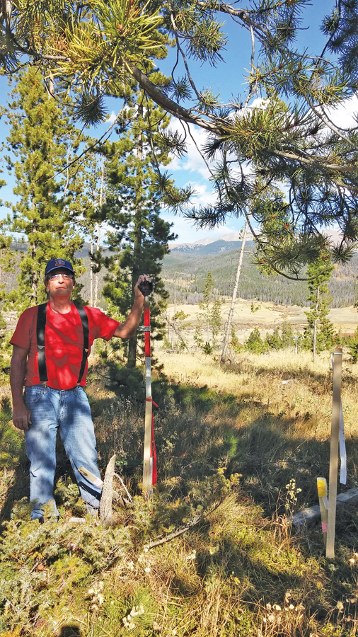 The author stands on the new aluminum cap, three feet from a plastic cap set 30 years prior, with the Continental Divide in the background. Credit: Pam Ward.