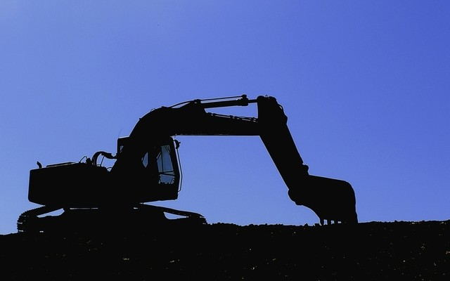 Digger silhouetted against a blue evening sky, crystal ball construction