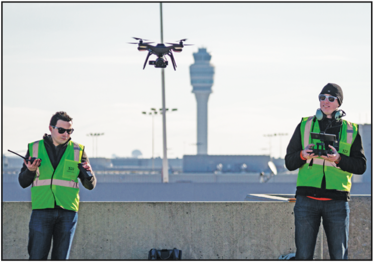 Nico Bonnafoux (left, Solutions Architect, 3DR) and Jeremiah Johnson (right, Solutions Architect, 3DR) take off with the Site Scan drone from the top deck of the north parking lot at Atlanta Airport.