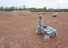 An ESA team member operates the rover on one of the team's tests sites.