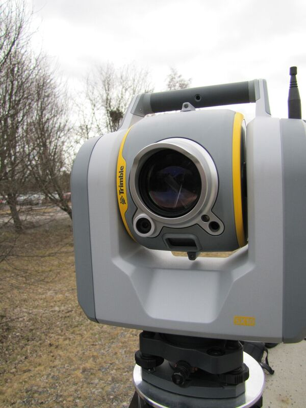 "Behind the distinctive ""bug eye"" of the SX10 is the spinning prism for scanning, a tracking laser, EDM laser, a tele-camera, and tracking camera. Flanking the lens is the overview camera (left) and primary camera (right), and a plummet camera underneath. Photo by G. Schrock"