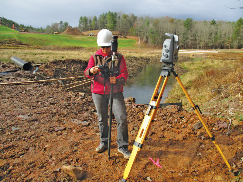 Evans sets up the Trimble VX total station to check elevations on the dam riser after surveying the riser top with the R10
