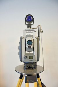 A total station and top-mounted prism as- sembly for reciprocal measurements. The prism rides in a rotatable bearing to provide stable orien- tation while the total station turns beneath it.