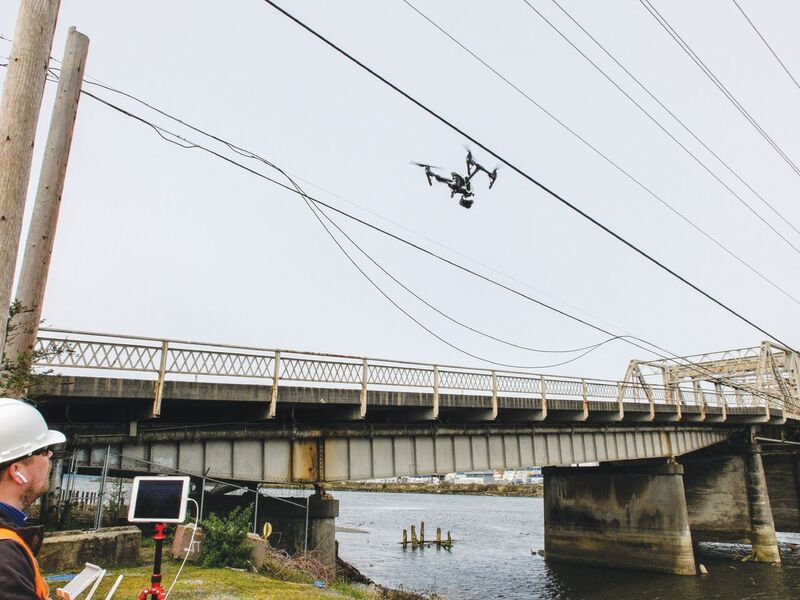 Kumpula (left) demonstrates an inspection maneuver for a remote pilot in training with a UAS near overhead utilities along the shut-down bridge.