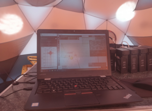 The team's main operations tent. Batteries can be seen on the right. GPR data can be seen on the left side of the laptop screen, drone route in the center and drone telemetry on the right.
