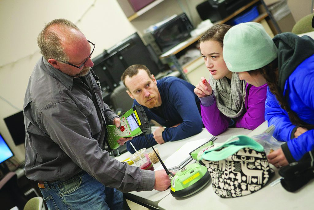 Prof. John Bean helps a group of students to understand new material. Credit: Phillip Hall, UAA.