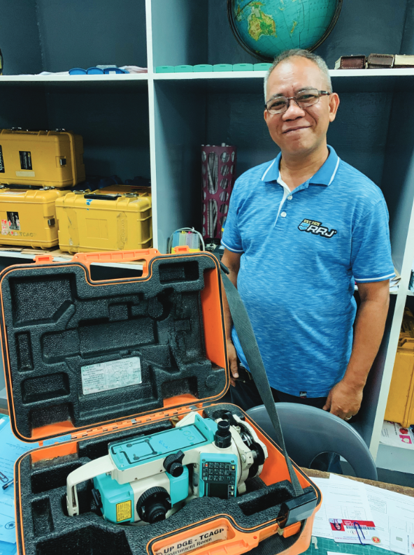 Luisito Pernia is the department's equipment custodian, shown here with a total station ready for students to use.