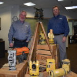 Mark Contino, vice president of North American retail distribution at Topcon Positioning Systems (left) and Ken Shersty, director of hardware sales for TSS, in a small museum of survey gear in The Solutions Store Kent, Washington, location.