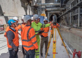 Working in the TBM access trench, a team uses a total station and handheld controller for automated measurement and data analysis.